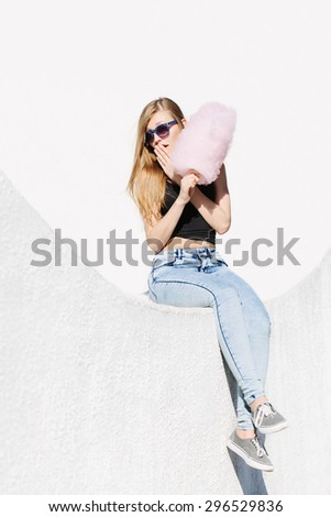 lifestyle portrait of beautiful surprised girl sitting outside with pink cotton candy. Wearing sunglasses. Red lips. White background, not isolated. - stock photo
