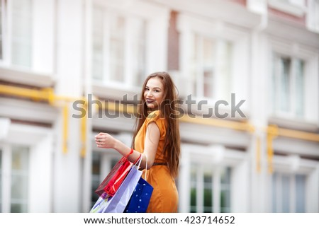 lifestyle portrait of cute cheerful young girl  shopping in city center, enjoying vacation, holding paper bags. - stock photo