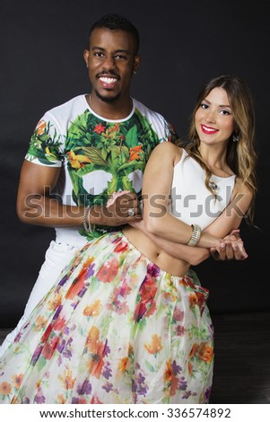 Lifestyle portrait of of happy smiling dance couple in hugs, holding hands. Wearing bright clothes with floral print. Smiling and dancing. The girl's make up arrow, red lips and curly blonde hair - stock photo