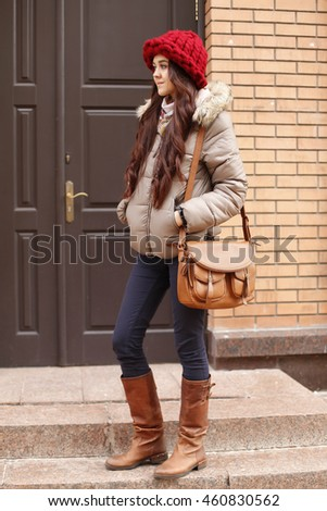 Lifestyle portrait of pretty young fashion smiling brunette woman in winter jacket, bright hat, shoes with leather bag posing outdoor in the street background in cold weather