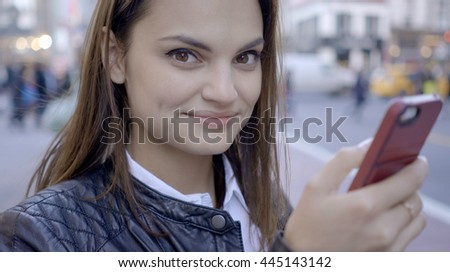 lifestyle portrait of young attractive caucasian women smiling at camera using smart phone device. beautiful stylish female model background