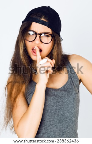 Lifestyle studio portrait of young cheeky pretty sportive girl having fun put her finger to the lips and say shhh , wearing trendy swag hat and hipster glasses. - stock photo