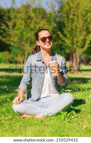 lifestyle, summer vacation, drinks and people concept - smiling young girl drinking coffee from paper cup and sitting on grass in park - stock photo