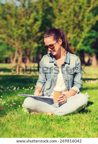 lifestyle, summer vacation, education, drinks and people concept - smiling young girl writing to notebook and drinking coffee in park - stock photo