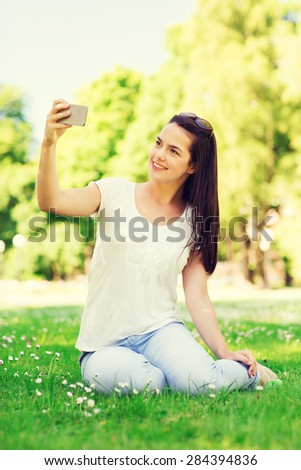 lifestyle, summer, vacation, technology and people concept - smiling young girl with smartphone making selfie and sitting on grass in park
