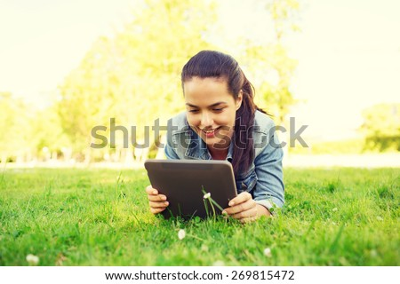 lifestyle, summer vacation, technology, leisure and people concept - smiling young girl with tablet pc computer lying on grass in park - stock photo