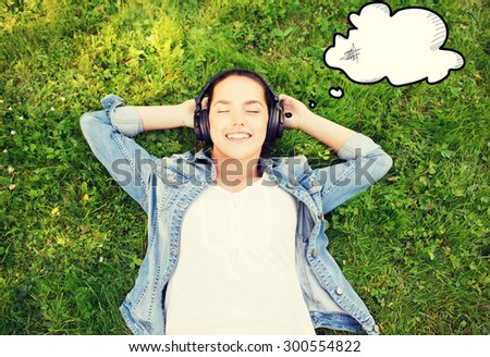 lifestyle, summer vacation, technology, music and people concept - smiling young girl in headphones lying with closed eyes on grass - stock photo