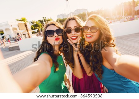 Lifestyle sunny image of best friend girls  taking selfie on  camera, crazy emotions , happy vacations, shopping  day. Wearing elegant dress, way hairstyle, sunglasses and red lips. - stock photo