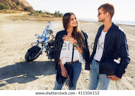 Lifestyle sunny portrait of young couple riders posing  together on  beach by motorbike - travel concept. Two people and bike .Fashion image of amazing sexy woman and man talk and laughing. - stock photo