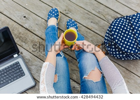 Lifestyle, vacation, education and people concept. Young hipster girl have a tea time outdoor - stock photo