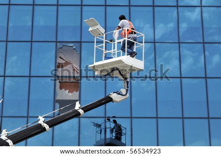 Lift operator breaks the windows of an office while cleaning them - stock photo