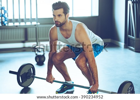 Lifting barbell. Young handsome man in sportswear lifting barbell at gym - stock photo