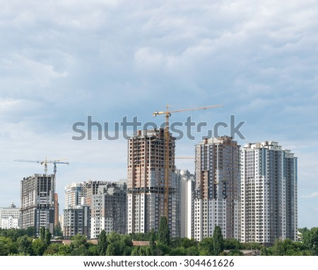 Lifting cranes and building under construction - stock photo