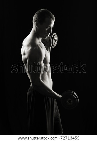 Lifting Weights, low key - stock photo