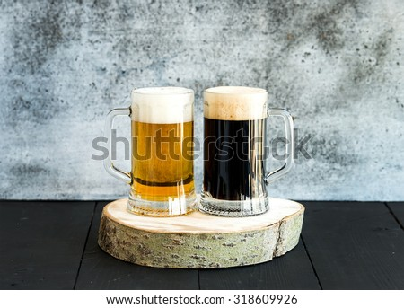 Light and dark beer in mugs on wooden board, grunge backdrop - stock photo