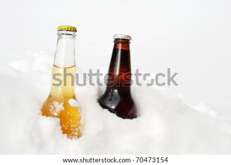 light and dark beer in the snow - stock photo