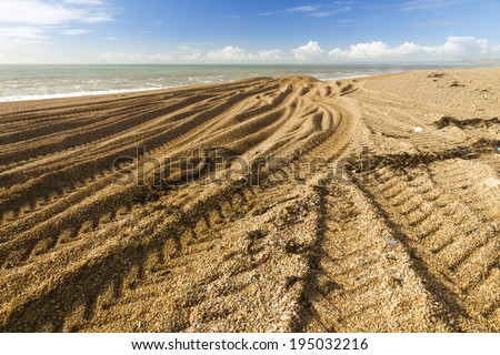 Light and shadow, beach made of pebbles with caterpillar tracks converging into distance.