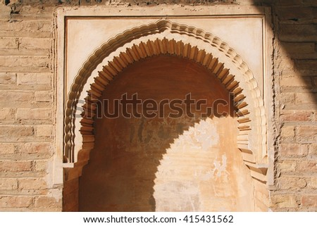 Light and shadow upon an arched niche on a stone wall of the Alhambra, Granada (Spain). - stock photo