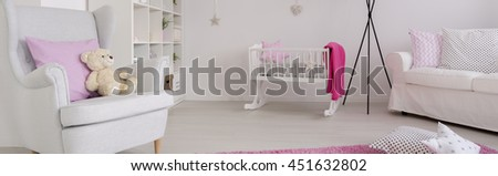 Light and spacious baby room with simple white furniture and pink details - stock photo