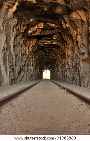 Light at the end of the tunnel. View inside a long railroad tunnel - bright light off in the distance.