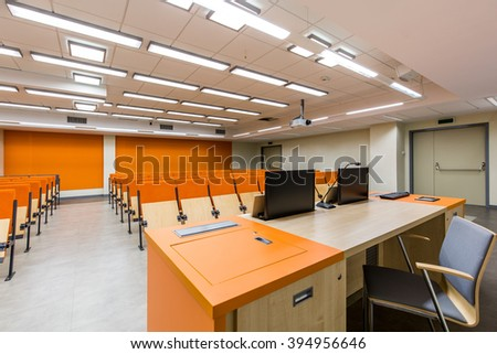 Light auditorium with orange details, wood desk and chairs - stock photo