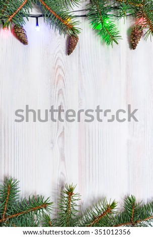 Light background with branches of fir and Christmas lights - stock photo