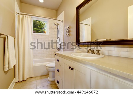 Light bathroom interior with white cabinet, shower with tile wall and tile floor. - stock photo