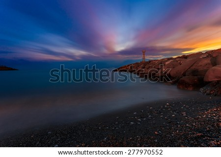 Light beacon and rocky wave breaker near Acroyali village, Messinia prefecture in Greece against a yellow sunset sky, long exposure photography - stock photo