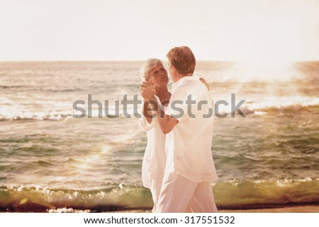 Light beam against retired couple dancing on the beach - stock photo