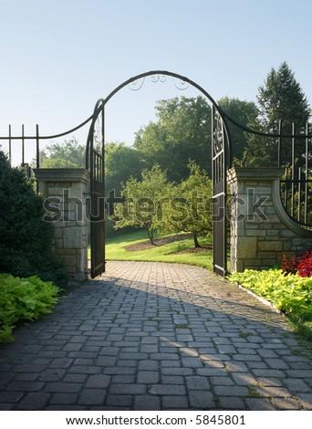 Light beckons through a stone and iron gateway. - stock photo