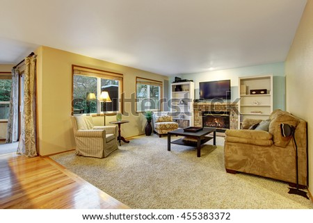 Light beige living room with sofa, armchair and cozy fireplace - stock photo