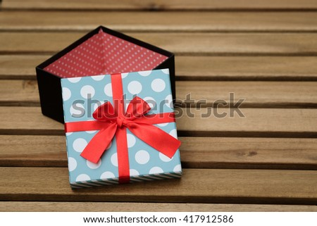 light blue and white polka dot with red ribbon gift box on wood table with green background - stock photo