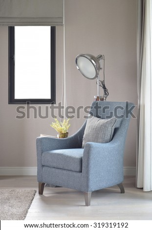 Light blue armchair with gray pillow and retro lamp in the living room - stock photo