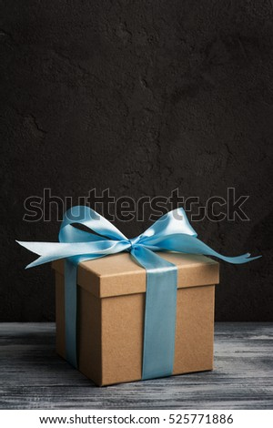 Light blue bow with handmade present box on shabby wooden background. Copyspace for text