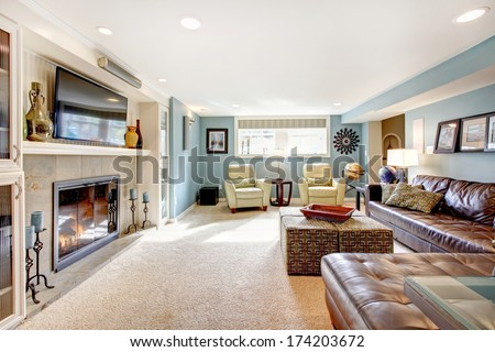 Light blue living room with leather furniture set, beige carpet floor, tv and fireplace - stock photo