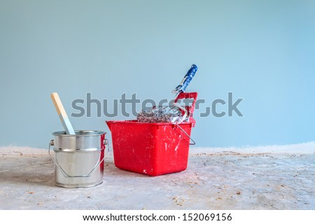 Light blue painted wall with painting tools in front on a concrete floor - stock photo