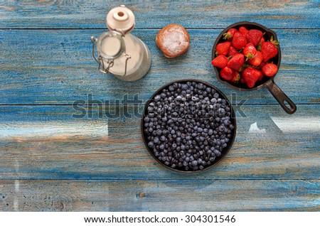 Light breakfast for the whole family, fresh berries spread in a bowl, bun with jam and a jug of milk lie next - stock photo
