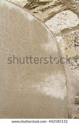 Light brown cracked mortar and part of the stone arc, background, copy space. - stock photo
