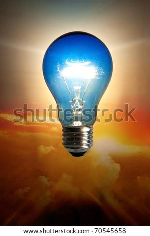 Light bulb abstract over sun set sky - stock photo