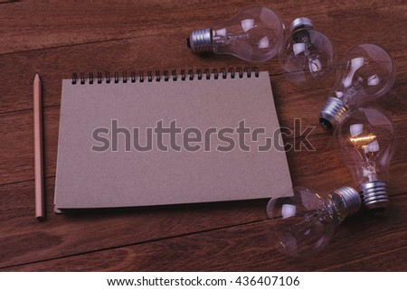 Light bulb and book on wooden table. Concept for workspace. Concept for leadership. Concept for idea. Concept for solution. - stock photo