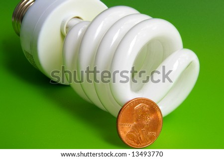 light bulb and penny, closeup on green background - stock photo