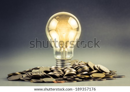 Light bulb and pile of coins