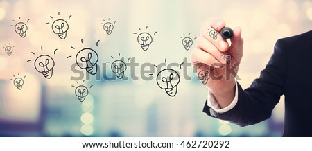 Light Bulb concept with businessman on blurred abstract background