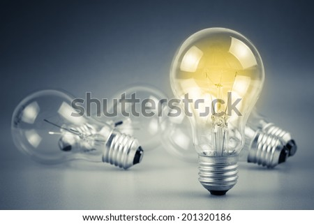 Light bulb glowing among the others - stock photo