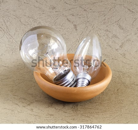 Light bulb in a ceramic bowl isolated on various backgrounds - stock photo