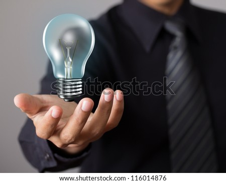 Light bulb in businessman hand - stock photo