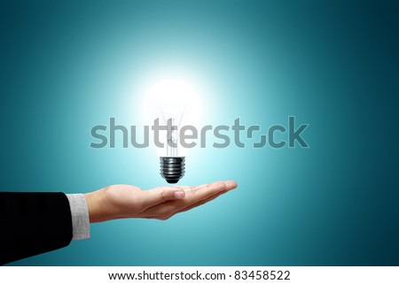 Light bulb in hand business woman on green background - stock photo