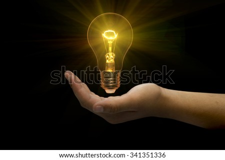 Light bulb in hand on black background.