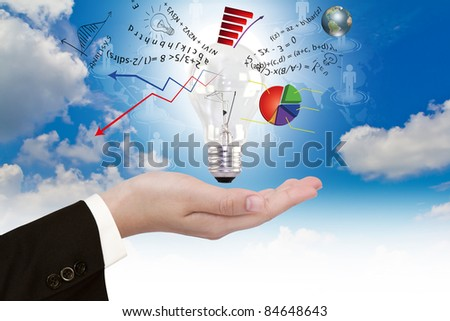 Light bulb in hand with graph out - stock photo