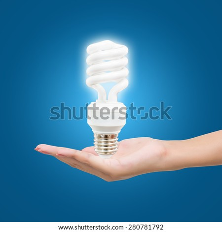 Light bulb in hand woman on blue background